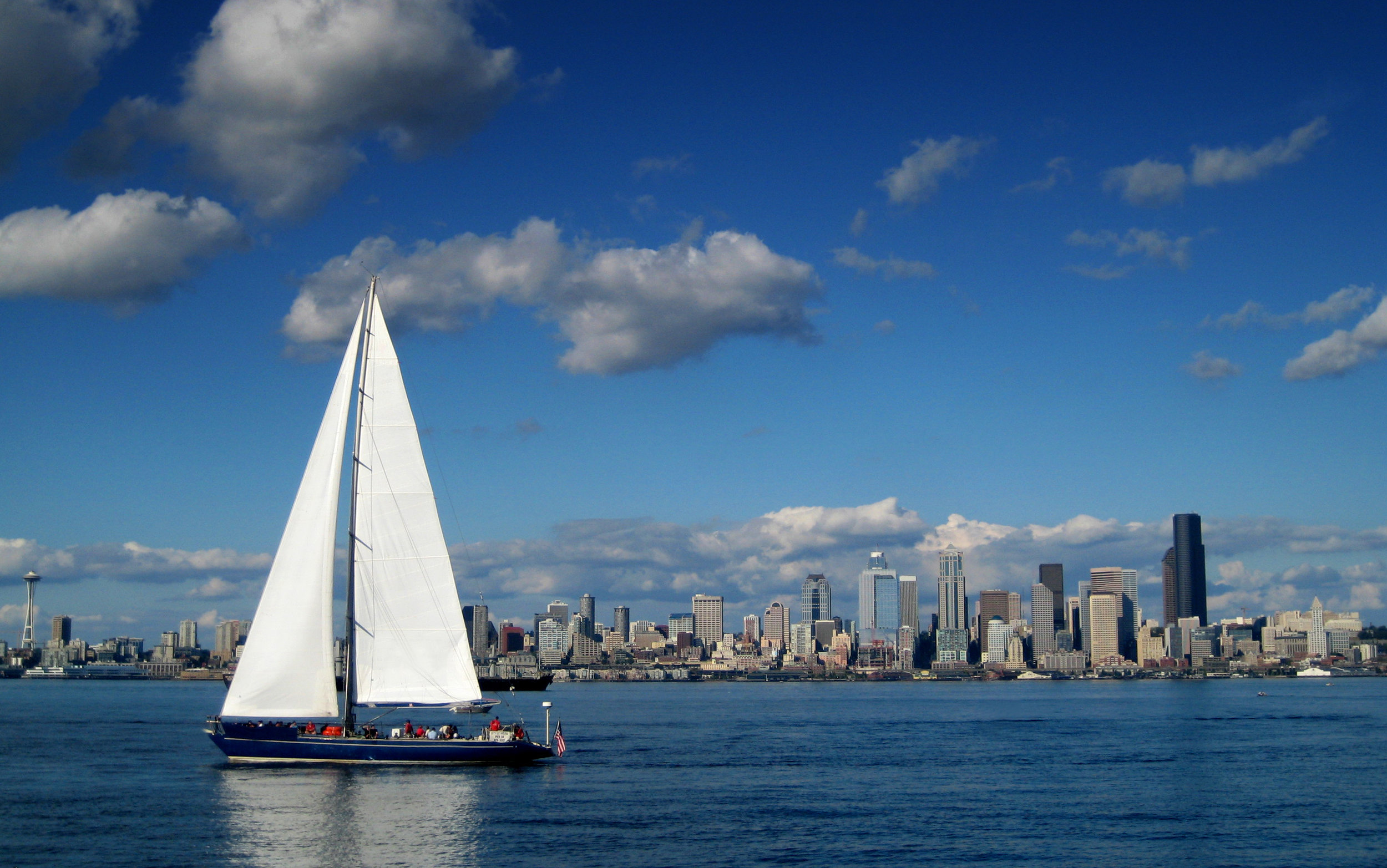 Seattle Skyline with a large sailboat in the foreground with the sails extending above the hoirzon. The Seattle Space Needle frames the left edge of the composition.
