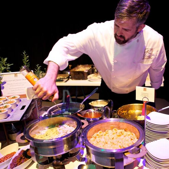 Kaspars Catering Chef saucing and serving food at Macaroni Action station at Gala Event. Hors d'Oeurves in the background.